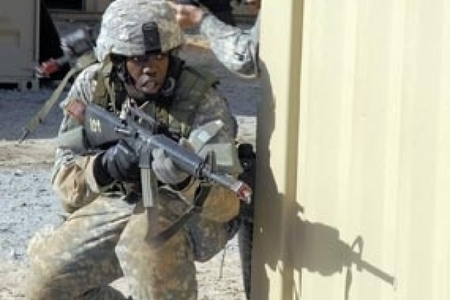 Pvt. Brande Sackinger, front, and Pfc. Maria Arango, both of Company D, 2nd Battalion, 13th Infantry Regiment, prepare to enter a building at the Military Operations on Urban Terrain site at Fort Jackson, S.C.
