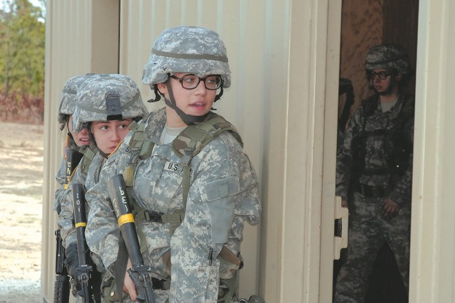 Pvt. Brande Sackinger, front, and Pfc. Maria Arango, both of Company D, 2nd Battalion, 13th Infantry Regiment, prepare to enter a building Friday at the Military Operations on Urban Terrain site at Fort Jackson, S.C.