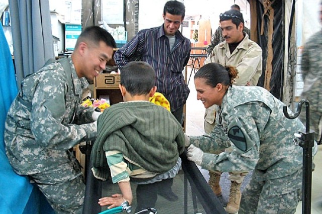 U.S. Army Capt. Thornton S. Mu treats Ibrahim, an 8-year-old boy who arrived at Forward Operating Base Sykes seeking medical attention. Mu works as a pediatrician when not on deployment.
