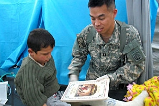 Capt. Thornton S. Mu shows a book to Ibrahim, an 8-year-old boy who arrived at Forward Operating Base Sykes seeking medical attention.