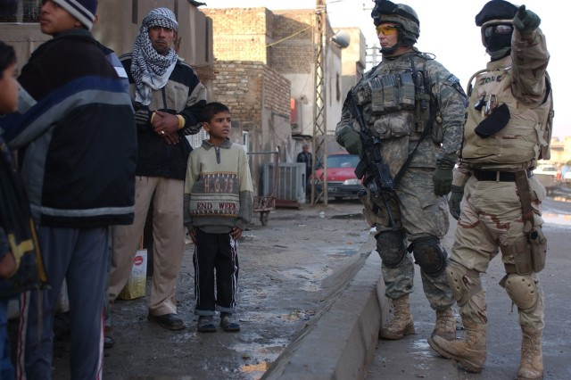 Sgt. 1st Class Michael Robinson and his Iraqi interpreter speak with area residents.