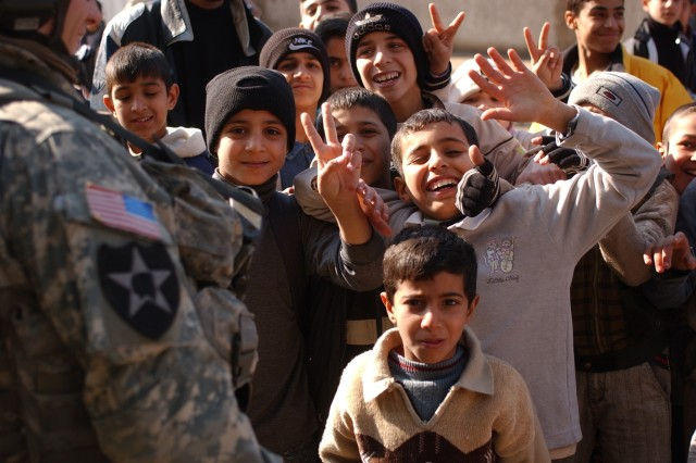 Children greet the Soldiers and ham it up for the camera.