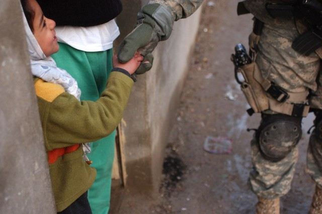 Sgt. 1st Class Michael Robinson greets an Iraqi child.