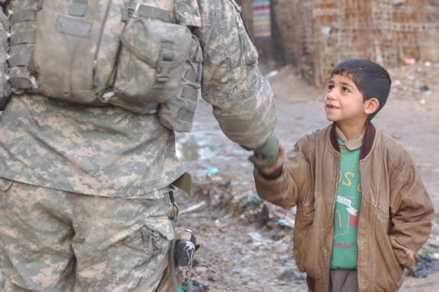 Another child greets a Soldier.