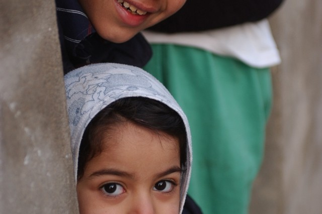 Iraqi children smile as the Soldiers depart their neighborhood.
