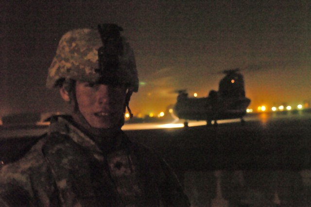 Spc. John Hamilton of Battery B, 2nd Battalion, 319th Airborne Field Artillery Regiment, 2nd Brigade Combat Team, 82nd Airborne Division, prepares to move off the flight line at Camp Taji in Baghdad Jan. 20 as the CH-47 Chinook helicopter that brought him lifts off again.