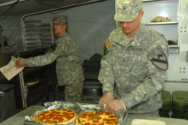 Staff Sgt. Jeffrey Lambert (left) and Pfc. Michael Minch, both food-service specialists for Company E, 2nd Battalion, 8th Cavalry Regiment, prepare Little Caesars pizzas for the Soldiers of Company B, 2nd Battalion, 8th Cavalry Regiment, in a mobile field kitchen in the Co. B motor pool Jan. 18 at Camp Taji, Iraq.