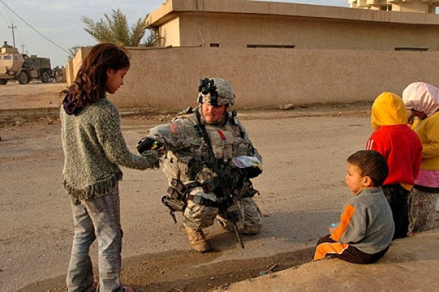 Sgt. 1st Class Bill Bowen, Company C, 1st Battalion, 149th Infantry Brigade, hands out candy and gum to children sitting outside the Al Hamdaniyah School in western Baghdad. Bowen, a native of Stanton, Ky., and members of Company C dropped off school supplies and backpacks for the 310 students attending the school.
