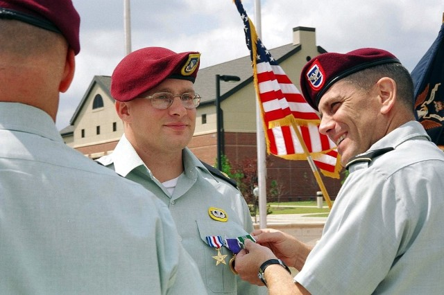 """Sgt. Tommy Rieman, B Company, 3rd Battalion, 504th Parachute Infantry Regiment, is awarded the Purple Heart by Col. Michael Ferriter during a ceremony at Devil Field, August 6. Rieman was also awarded the Silver Star and Army Commendation medal with """"V"""" device for heroism during an ambush in Iraq last year."""