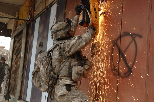 A Soldier uses a power saw to cut the locks off the door of a building suspected of containing a weapons cache.