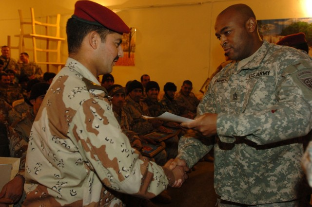 Sgt. Maj. Samuel Campbell, the task force sergeant major for 1st Battalion, 319th Airborne Field Artillery Regiment, presents a certificate of achievement to a 9th Battalion, Strategic Infrastructure Brigade soldier at his graduation from a new non-commissioned officer (NCO) course in Tikrit, Iraq, on Wednesday. The NCO training course was established and staffed by U.S. Soldiers from 1-319th AFAR stationed out of Contingency Operating Base Speicher.