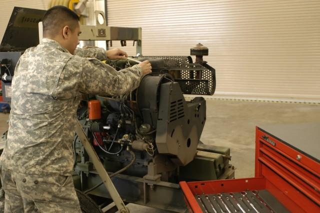 Sgt. Frank Avila works on a fuel pump in the motor pool bay.