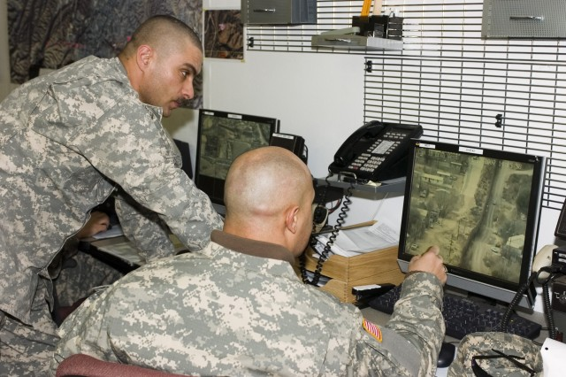 National Guard Soldiers discuss live border surveillance images.