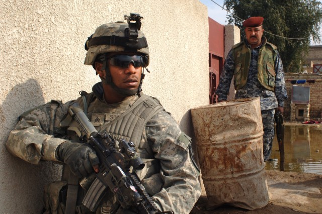 Sgt. Domonic Simpson, from the 2nd Brigade Combat Team, 2nd Infantry Division, provides security as Iraqi security forces conduct a cordon and search operation in the Karmaliyah area of Baghdad, Jan. 16.