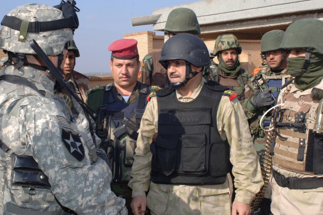 Lt. Col. James Phillips, commander, 3rd Squadron, 61st Cavalry Regiment, and the Iraqi commander of the 2nd Brigade, 1st National Police Division, discuss an operation in the Salman Pak area of southeastern Baghdad, Jan. 14.
