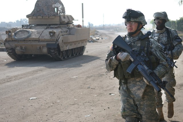 Spcs. Eloy Pena and Gregory Guyton, from the 1st Cavalry Division, move to their Bradley fighting vehicle during a combined cordon and search mission in Ghazaliya, Iraq.