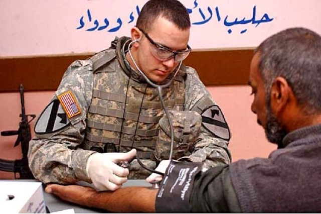 Pfc. Daren C. Ruby from Sand Springs, Okla., a combat medic with the 2nd Battalion, 82nd Field Artillery Regiment takes an Iraqi man's blood pressure before he is diagnosed in Al Jamiah, Jan. 15.