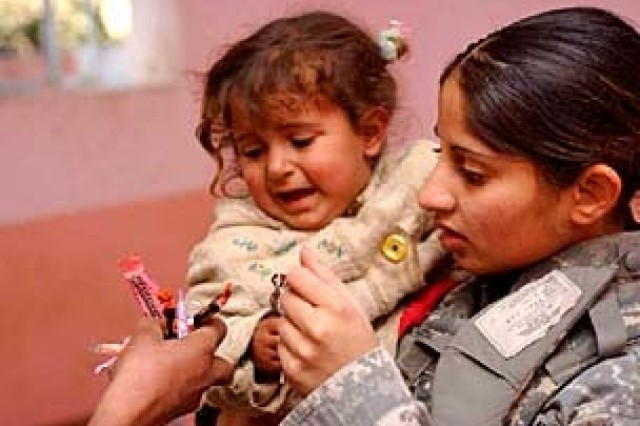 Sgt. Rosy Hart, a native of Manheim, Germany and an administrative assistant, gives an Iraqi infant candy at a day-clinic in Al Jamiah, Jan. 15.