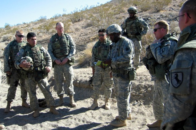 "Sgt. Steve Smith (center), an observer-controller at the National Training Center at Fort Irwin, Calif., takes members of 1st Platoon, 58th Combat Engineer Company, through a ""hot wash"" or after-action review after they go through a route-clearing training course in preparation for deployment to Iraq."