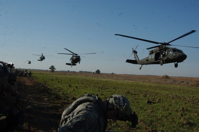 Soldiers from the 2nd Battalion, 15th Field Artillery Regiment, 2nd Brigade Combat Team, 10th Mountain Division and Iraqi Army Soldiers from 1st Battalion, 4th Brigade, 6th Iraqi Army Division wait as U.S. Army UH-60 Black Hawk helicopters approach their drop zone near Mahmudiyah.