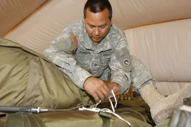 Sgt. Harvey Johnson ties down supplies for a heavy drop.