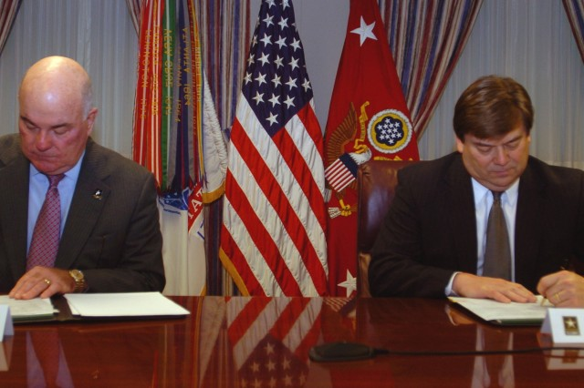 Secretary of the Army Francis J. Harvey (left) and Raytheon Corporation Vice President for Human Resources Keith Peden sign formal agreements making Raytheon the 200th member of the Army's Partnership for Youth Success program.