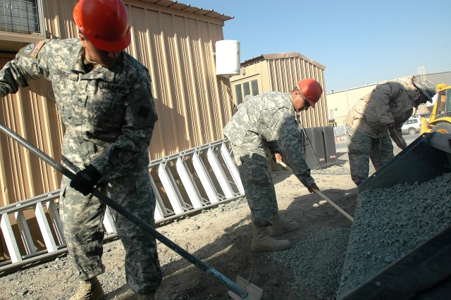 Engineers from Detachment 2, 863rd Engineer Battalion spread gravel on rough ground at Camp Arifjan, Kuwait, Jan. 4.