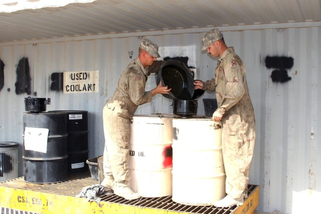 Mechanics from the Third Army in Kuwait dispose of used motor oil.