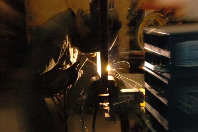 Sgt. John Klempnow, a welder with the 3rd Battalion, 82nd Field Artillery Regiment, 2nd Brigade Combat Team, 1st Cavalry Division, carefully guides the electric arc from his welding rod across a joint while working on a project at Forward Operating Base Union III.