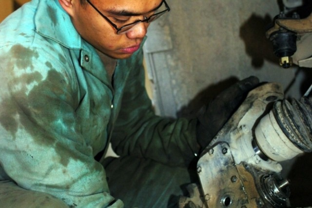 Spc. John Samson from Headquarters and Headquarters Company, 3rd Battalion, 82nd Field Artillery Regiment, 2nd Brigade Combat Team, 1st Cavalry Division, works on repairing a wheel-hub assembly at the battalion's motor pool on Forward Operating Base Union III. Samson and his platoon have serviced more than 100 vehicles for the battalion and hundreds more for the other coalition elements on the base.