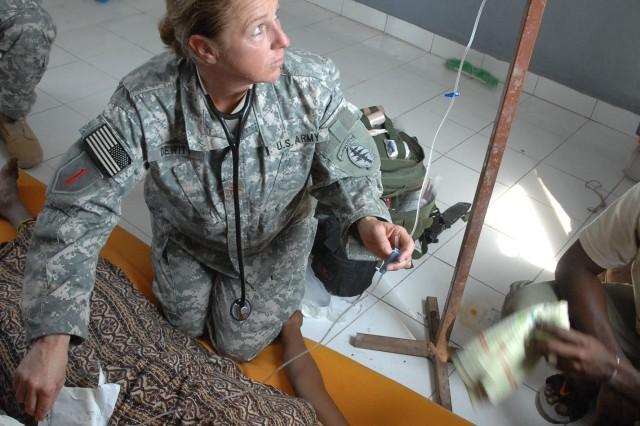Maj. Lisa J. Dewitt administers medicine to a woman having a seizure. Dewitt is participating in a medical civic action program in Sagallou, Djibouti, Jan. 23.