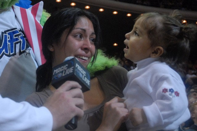 Alma Anderson cries as she is told of an incoming video call via Jumbo-tron from her husband Ryan, who is stationed in Iraq. Looking on is her 16-month old daughter Isabel.