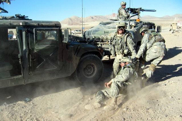 "Medics from the 3rd Infantry Division's 2nd Battalion, 69th Armor Regiment, pull a ""wounded"" comrade to a Humvee after a simulated improvised-explosive-device attack at the National Training Center. at Fort Irwin, Calif."