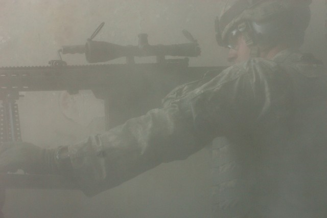 Sgt. Sean Milligan, from the 3rd Stryker Brigade Combat Team, 2nd Infantry Division, fires on insurgents through the smoke and dust of a building in downtown Baghdad, Jan. 24.