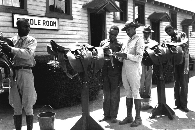 Capt. Merrel Moody instructs Privates Enichel Kennedy, Oscar Davis, B. D. Kroninger and Will Johnson of Infantry School Stables, on the proper way to clean a saddle at Fort Benning, Ga., July 25, 1941.