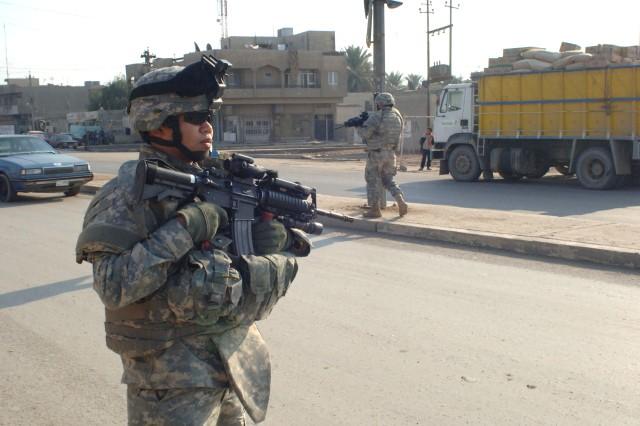Soldiers from the 2nd Infantry Brigade Combat Team, 2nd Infantry Division provide security during a patrol in the Zafaraniyah area of Baghdad.