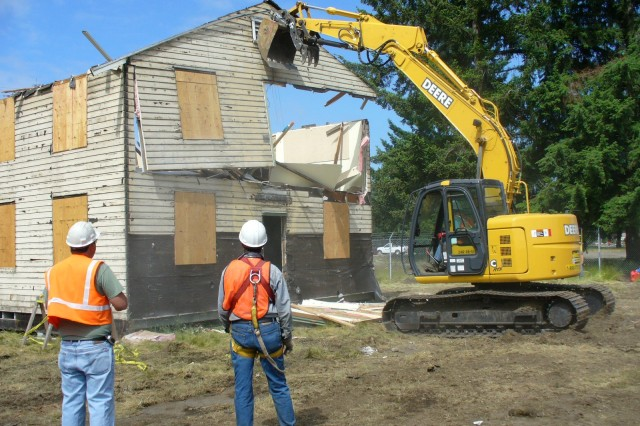 Workers remove a panel from a building at Fort Lewis, Wash., during modular deconstruction.