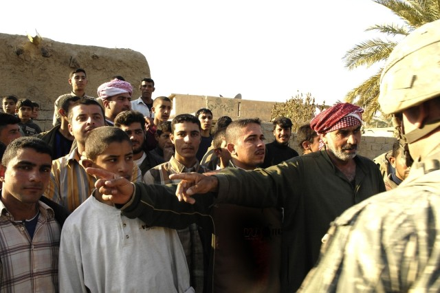 2nd Lt. Scott Siggens questions local villagers about mortar holes in Abu Nural.