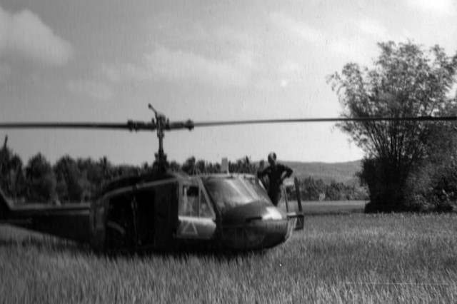 The venerable UH-1 Huey sits in a rice paddy between combat flights, Vietnam, 1966.