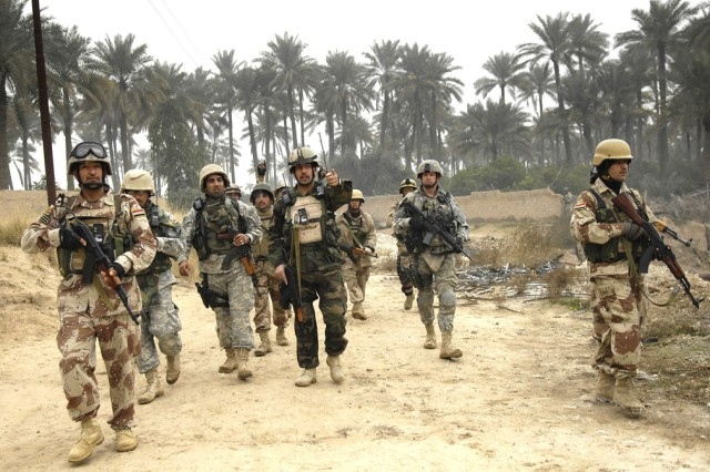 The Iraqi and U.S. Soldiers march together toward the village of Chubinait.