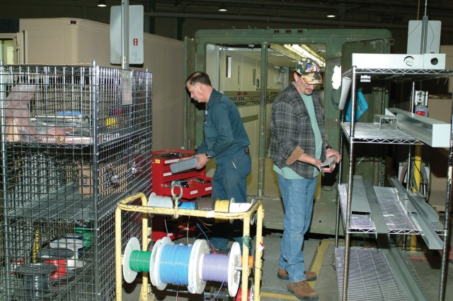 Robert Sukel, left and Thomas Hooper use new kits, packages and toolbaxes during the raceway installation process on an electronics repair van.  Electricians were able to cut travel, distance and repair time by placing the wheeled carts near the worksite.