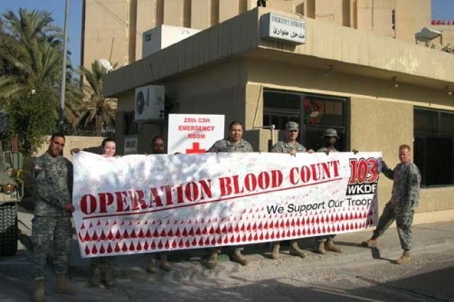 Soldiers in front of the 28th Combat Support Hospital (CSH) in Baghdad, Iraq proudly display a banner with signatures of support from military blood donors. The banner was signed during a National Guard blood drive held on 28 September 2006 in Nashville, Tenn. Country music sensation Aaron Tippin and wife Thea Tippin also signed the banner during the drive and thanked donors for their generous contributions to the troops. Thanks to the support of military blood donors, the Armed Services Blood program collected more than twice the amount of blood expected.