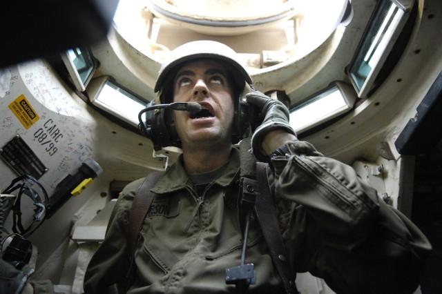 Sgt. 1st Class Michael Gibson directs a convoy of M1A2 Abrams tanks down a road in Kahn Bani Sahd.
