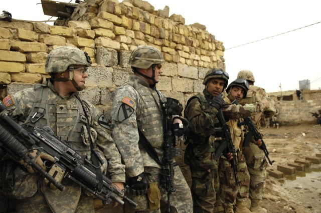 The Soldiers pause for cover at a wall and prepare to move out to their next objective.