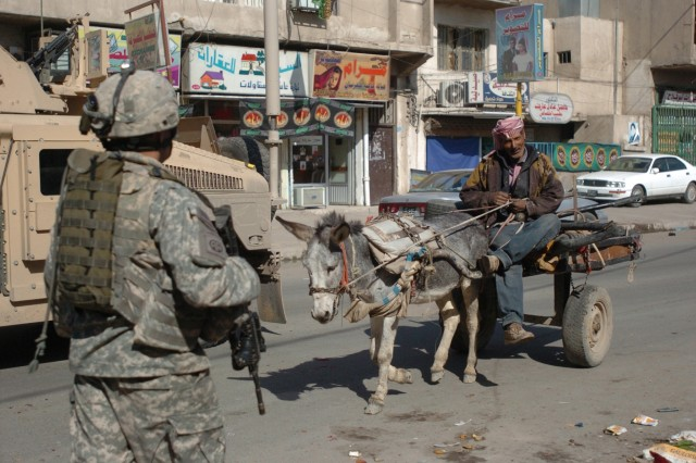 Sgt. John Pruitt, a squad leader with 2nd Platoon, Company A, 1st Battalion, 325th Airborne Infantry Regiment, 2nd Brigade Combat Team, 82nd Airborne Division, which is attached to 2nd BCT, 1st Infantry Division, passes a local Iraqi on the streets of the Hurriyah neighborhood of the Kadhimiya district of Baghdad Feb. 8. The Joint Security Station, where Pruitt resides, encourages transition by allowing Iraqi Security Forces to train with Paratroopers on a one-on-one basis.