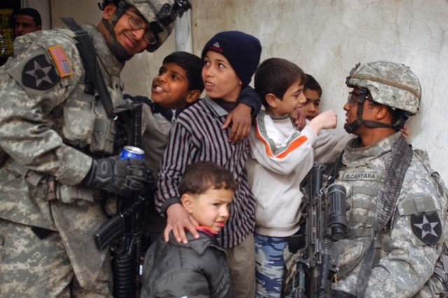 Spcs. Karreem Khan and Juan Alcantara interact with Iraqi children.