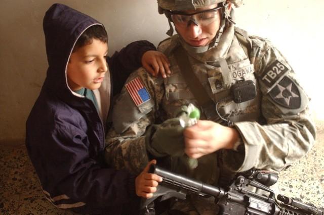 Sgt. 1st Class Daniel Ogawa opens a lollipop for a boy while taking a break.