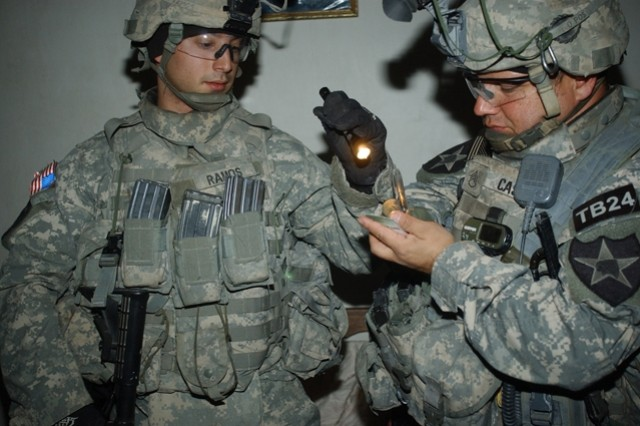 Spc. Victor Ramos (left) and Staff Sgt. George Castro gather intelligence.