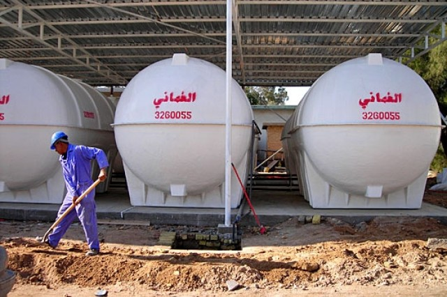 An Iraqi laborer works to prepare for the installation of a chain link fence to protect the storage tanks at the Umm Qasr water treatment facility.