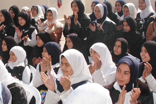 Students applaud during the opening ceremony earlier this week of a new girls' high school in north Baghdad. The $470,000 project includes 16 classrooms that handle an enrollment of up to 450 students. Ali Bunni, the Qada Council's deputy chairman, said during the ceremony that he could not adequately express in words his community's happiness about the new facility.